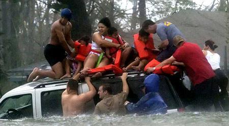 图文:飓风救援小组正将一家人从车顶上救下