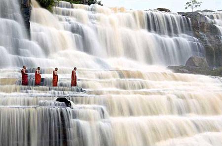 图文:越南达拉佛教僧侣从磅古瀑布旁走过