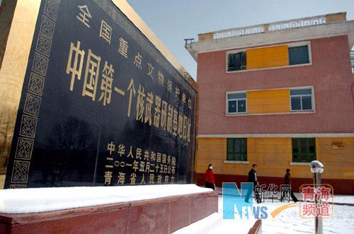 几名当地居民经过中国第一个核武器研制基地旧址纪念碑