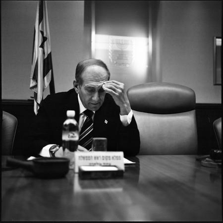 图文:奥尔默特坐在沙龙总理的空椅子旁