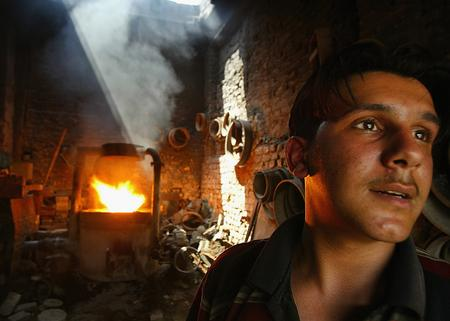 图文:一名正在照看自己店铺的伊拉克铁匠