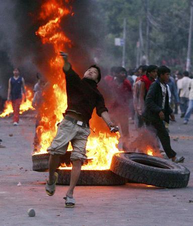 图文:抗议者向警察投掷石块反对国王统治
