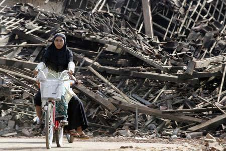 图文:地震幸存者骑车经过一片房屋废墟