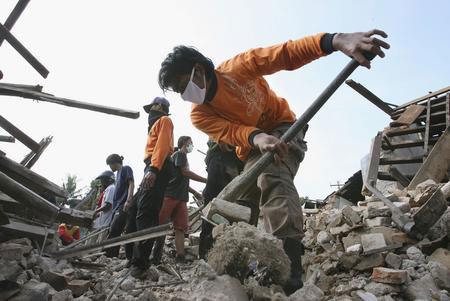 图文:志愿者在房屋废墟中寻找遇难者