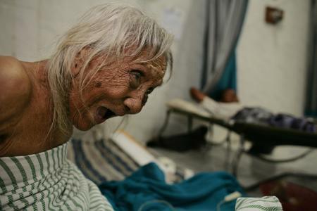 图文:一名年老的印尼妇女大声呼唤护士