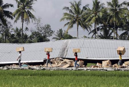 图文:幸存者从房屋废墟中捡拾可用物品