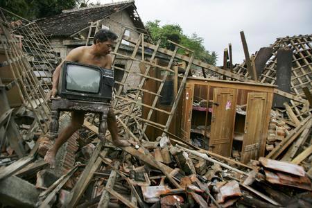 图文:村民从被毁的家园中搬出电视机