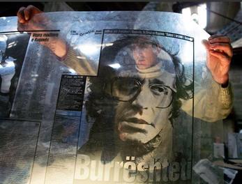 图文:工人将前科索沃总统照片放在封面