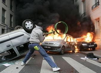 图文:法国男子向燃烧的汽车扔垃圾袋