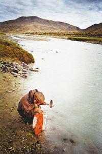 西藏阿里马攸木拉山,在河里取生活用水的孩子。